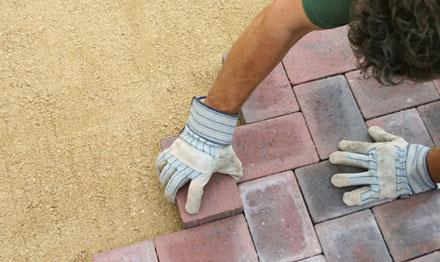 man laying block paving